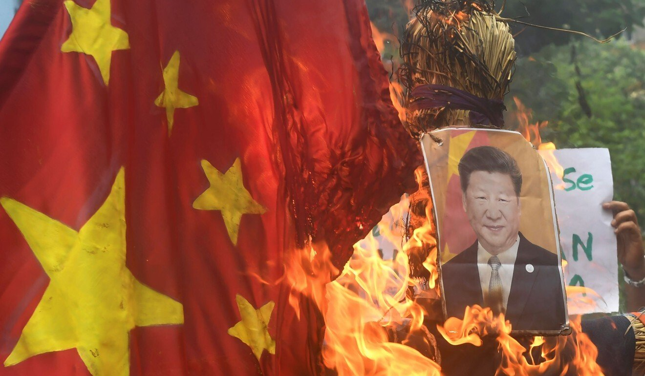 Indian protesters burn a Chinese flag and picture of Xi Jinping in a protest following a deadly clash between soldiers. Photo: AFP
