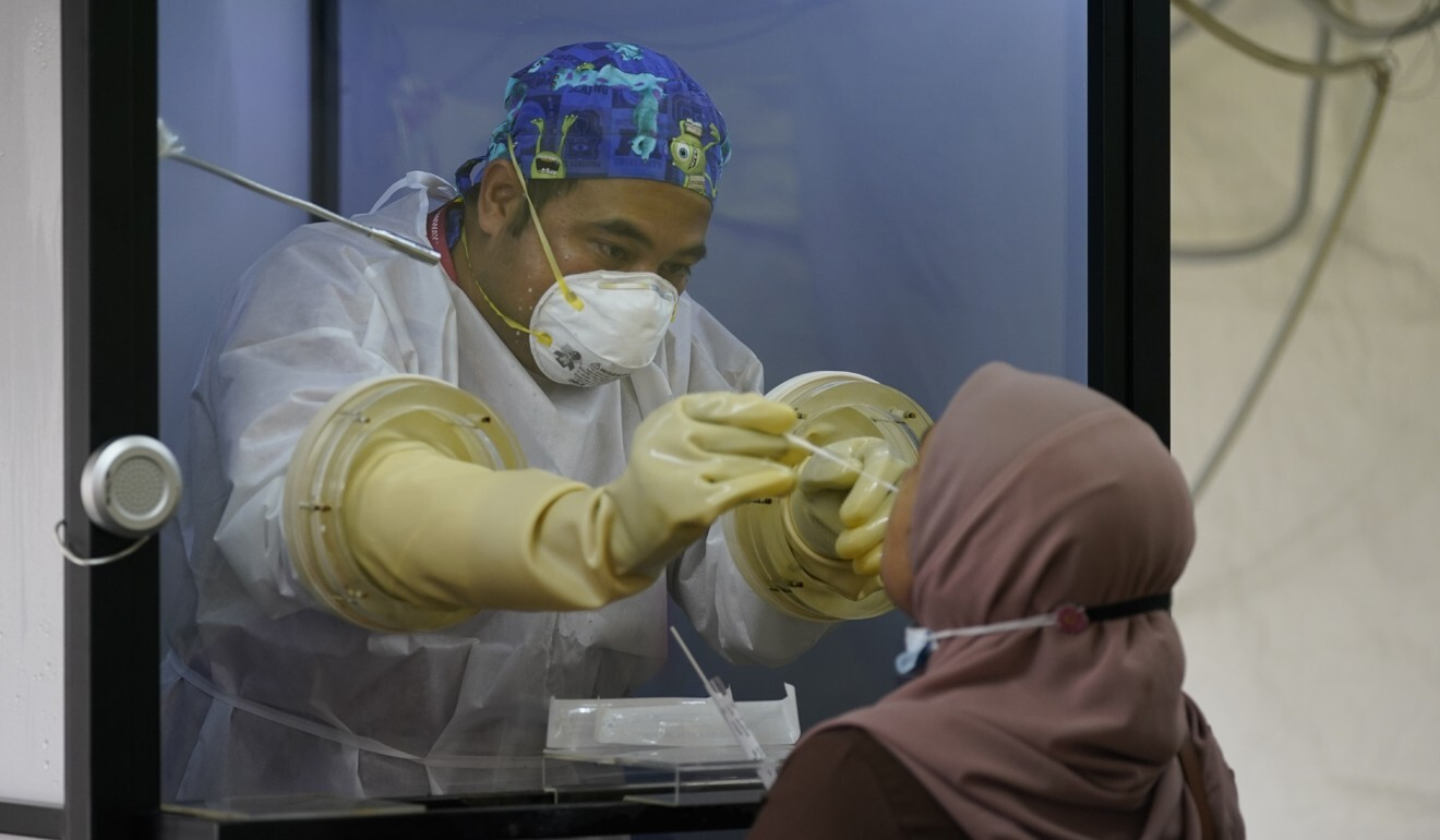 A doctor collects samples for a coronavirus test from behind a shield at a private hospital in Sunway, outside Kuala Lumpur, on Wednesday. Photo: AP