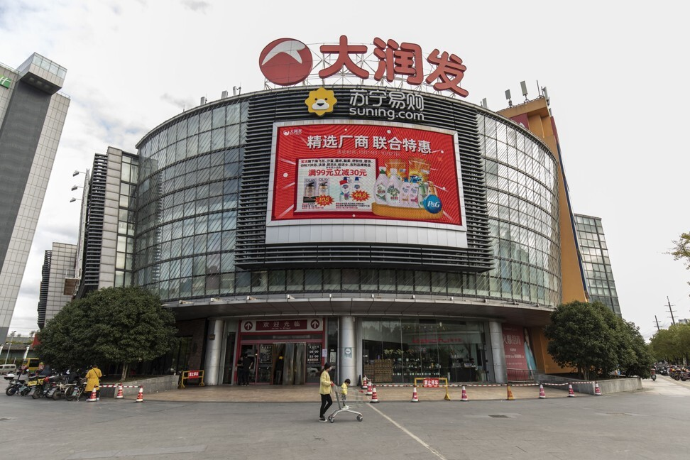 A person pushes a child in a shopping trolley past an RT-Mart hypermarket, operated by Sun Art Retail Group, in Shanghai, on October 19. Photo: Bloomberg