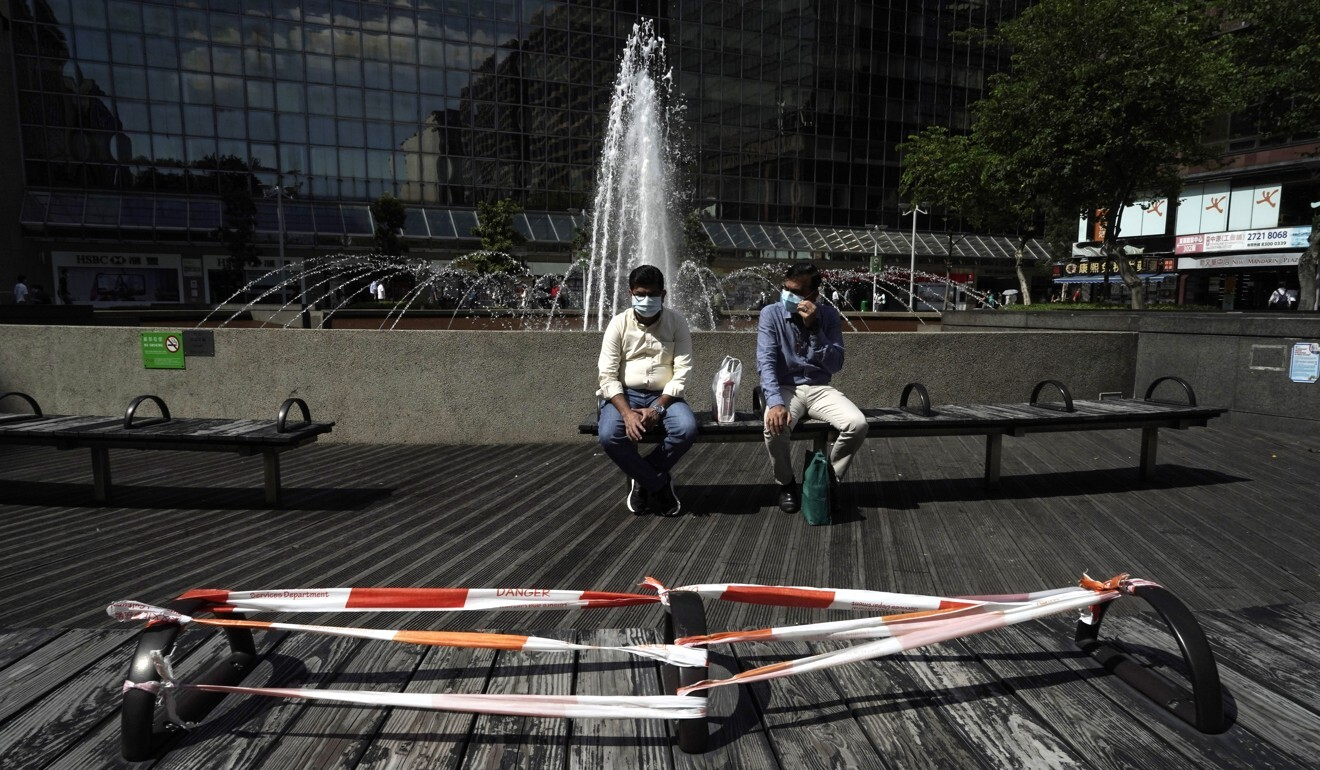 People wearing masks sit across from a bench that has been taped off to maintain social distancing in a Hong Kong park earlier this month. Photo: AP