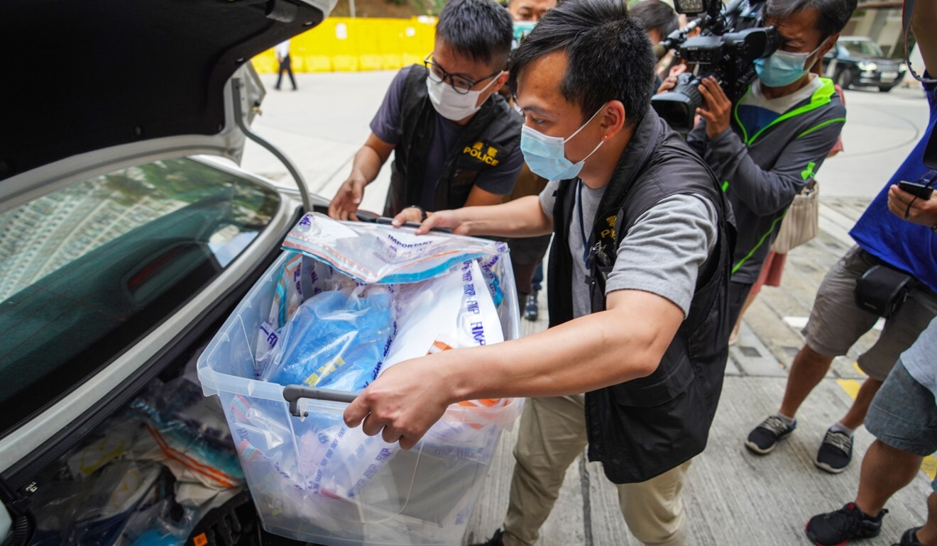 Police officers take away evidence gathered at the scene. Photo: Winson Wong