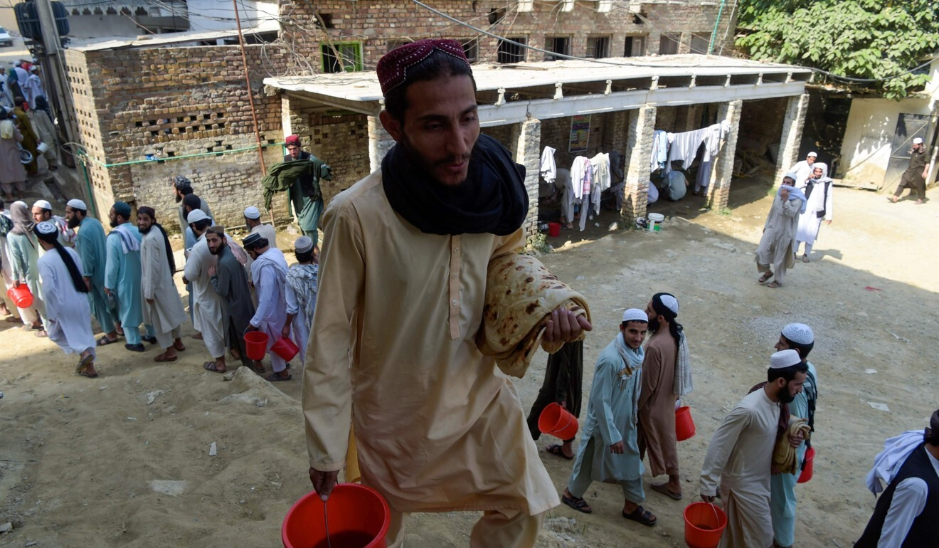 Islamic seminary students wait to collect food at the Darul Uloom Haqqania seminary in Akora Khattak. Photo: AFP
