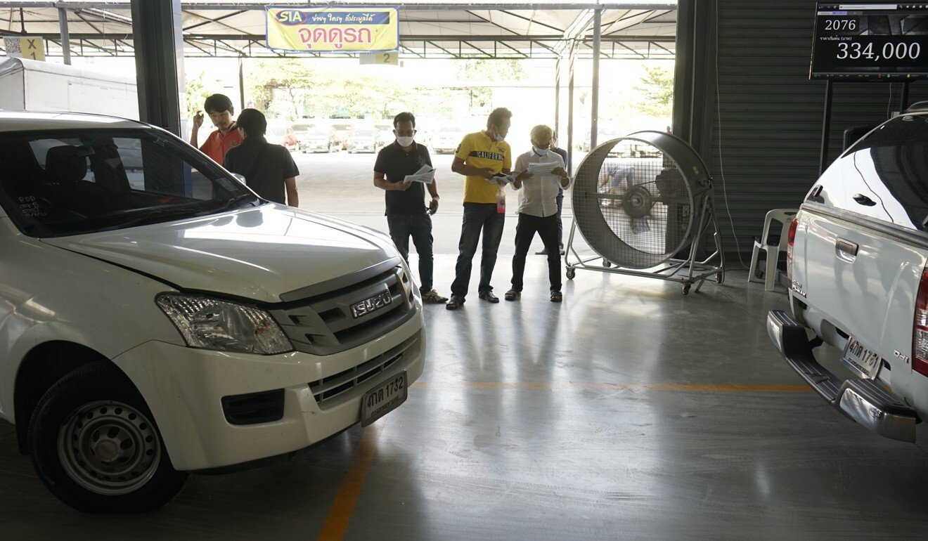 Potential buyers assess lists of second-hand cars at the SIA warehouse. Photo: Vijitra Duangdee