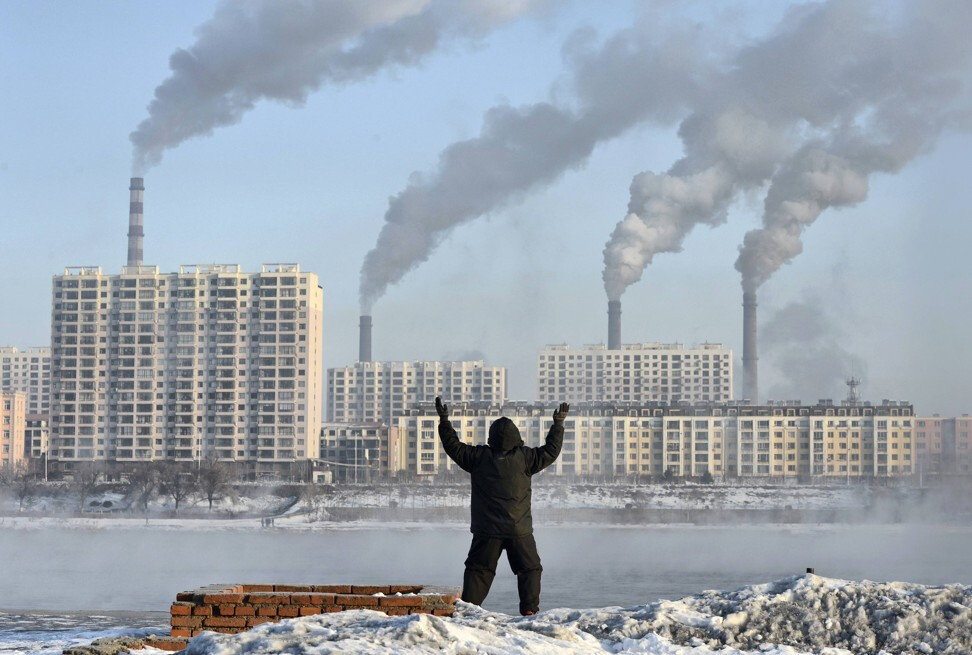A man doing his morning exercises in front of chimney stacks across the Songhua River in Jilin province on February 24, 2013. Photo: Reuters
