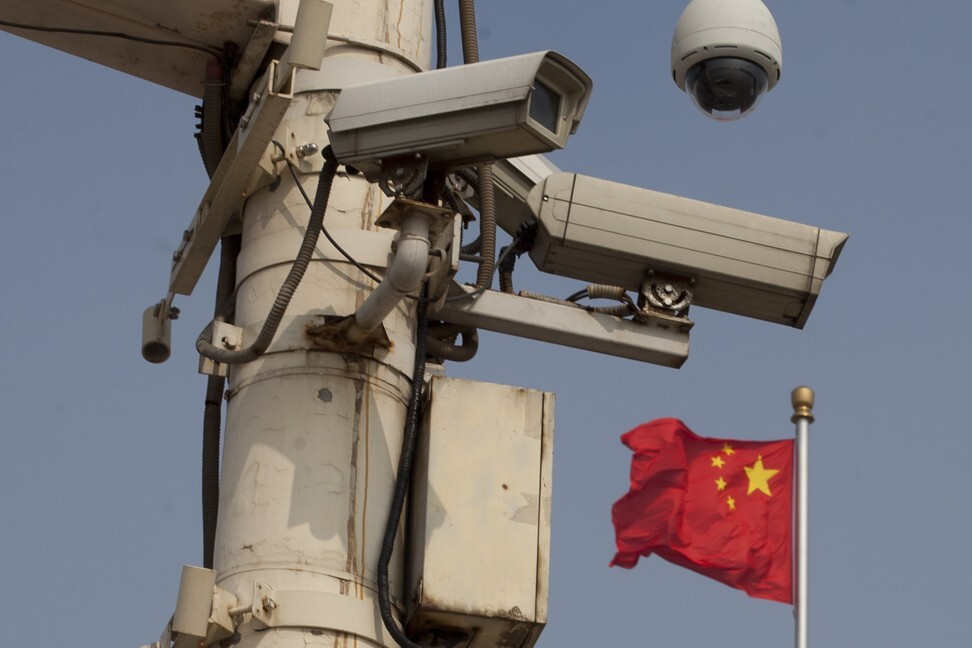 The Chinese national flag flies behind security cameras on Tiananmen Square in Beijing. Photo: AFP