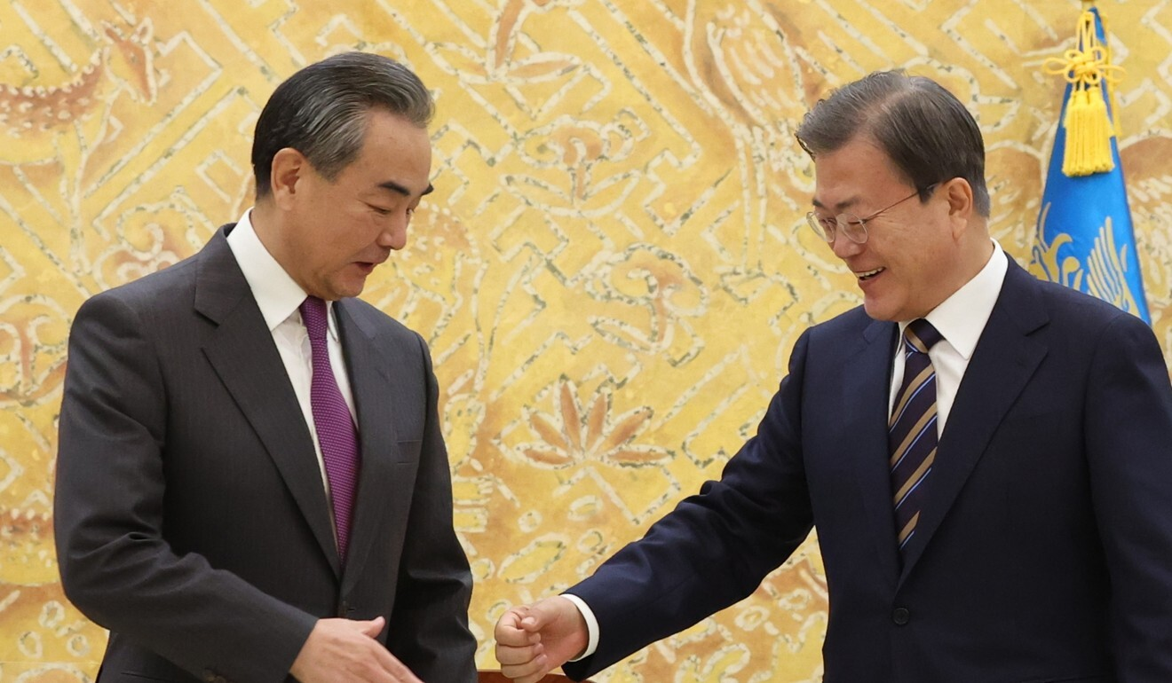 Chinese Foreign Ministry Wang Yi briefly hesitates as South Korean President Moon Jae-in offers a fist bump. Photo: EPA-EFE
