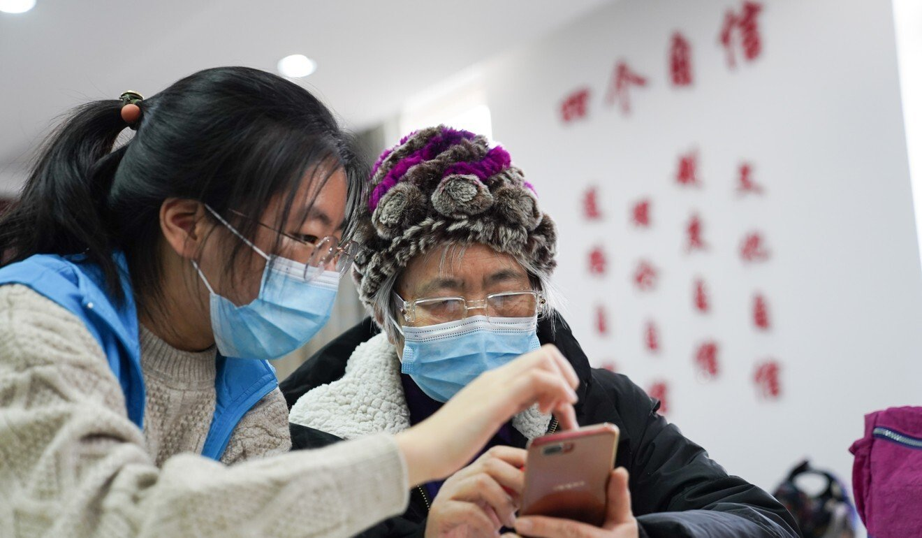 A volunteer from Beijing Foreign Studies University teaches an older woman how to use a health-tracking app on her smartphone. Photo: Xinhua