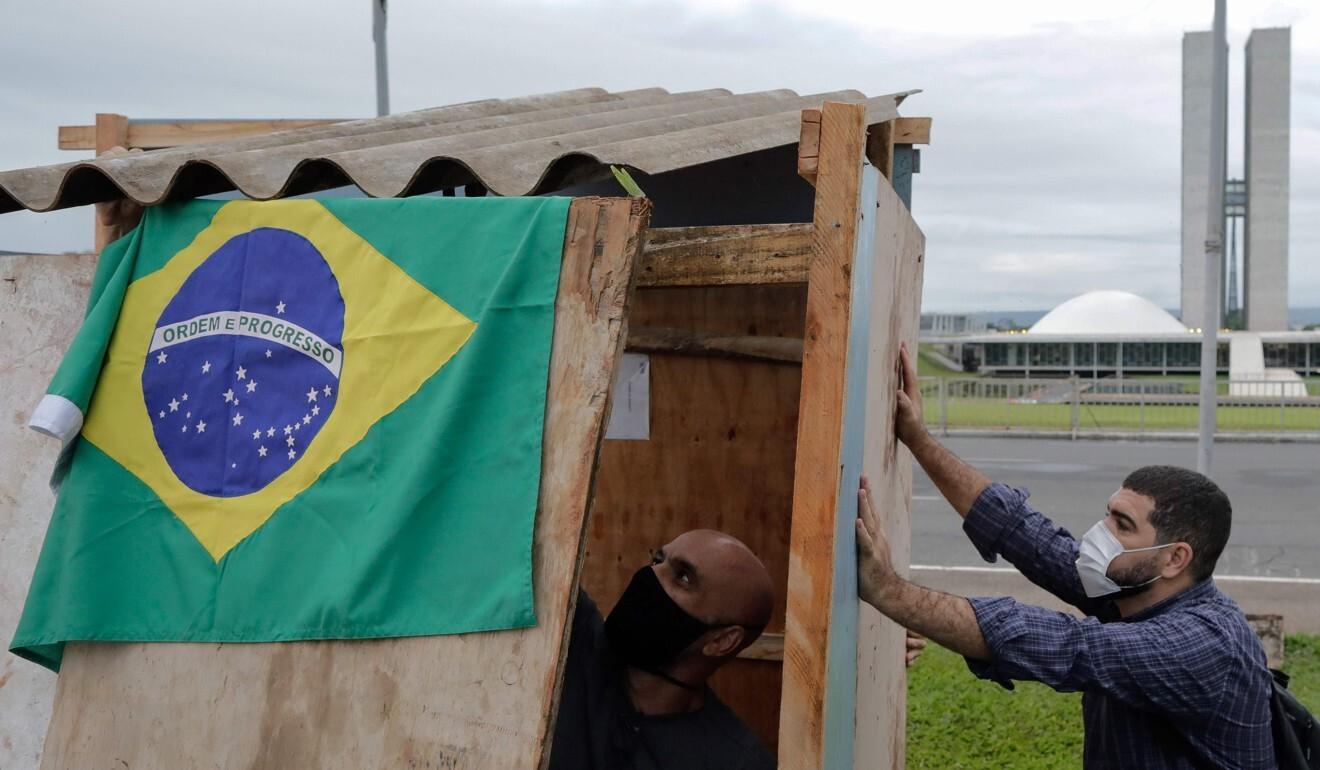 """Ativistas da organização não governamental """"Rio de Paz"""" erguem barracos simulados, que representam a vida de famílias de favelas de baixa renda no Brasil, para protestar contra a decisão do governo Bolsonaro de suspender a ajuda às pessoas mais afetadas pela pandemia.  Foto: AFP"""