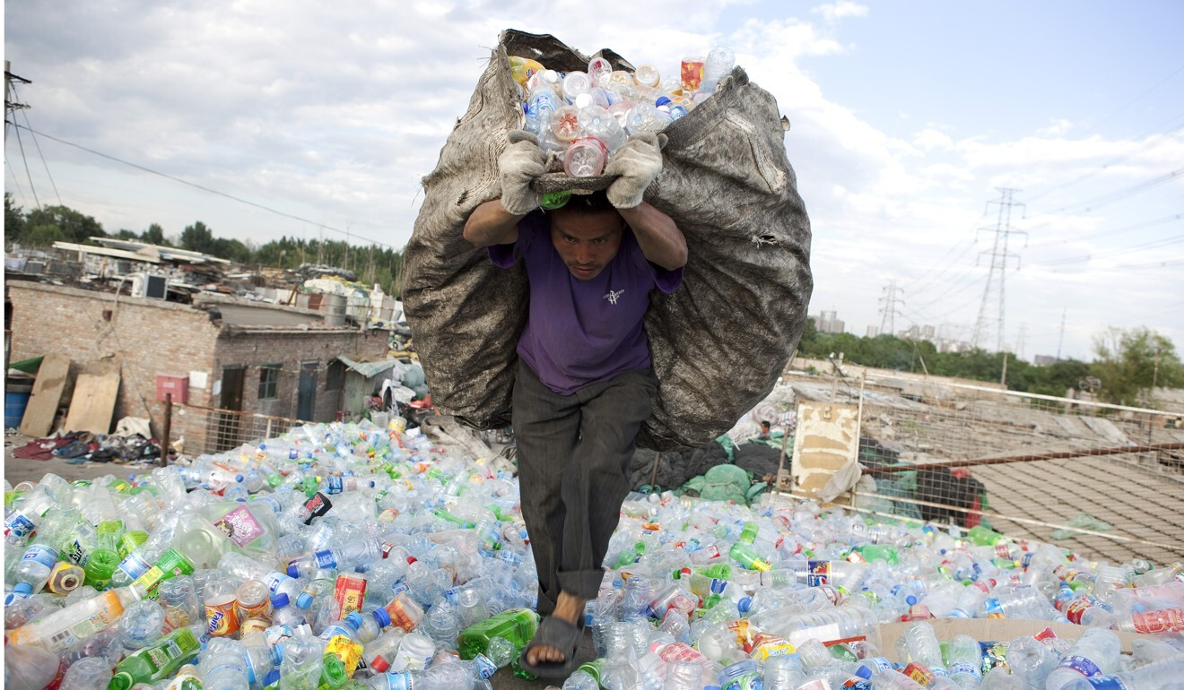 Workers carry and organise plastic bottles in Dongxiaokou village on the outskirts of Beijing. Photo: Getty Images