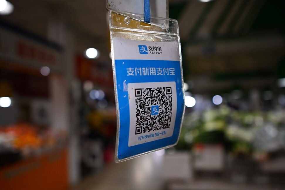 An Alipay QR payment code hangs above a stall for customers to scan with their smartphones to make electronic payments for items on the spot, at a market in Beijing on November 3, 2020. Photo: AFP