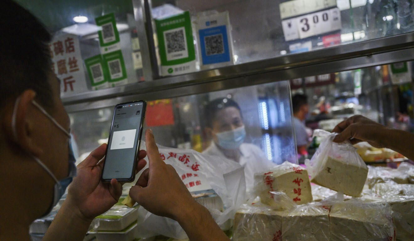 A customer uses his mobile phone to pay via a QR code using the WeChat app at a Beijing market. Elderly street vendor Zhang Baohua uses a QR code to receive payment for the salted duck eggs he sells, but has no idea where the money goes or how to retrieve it. Photo: Kevin Frayer/Getty Images