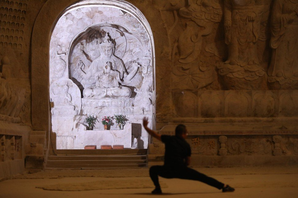 A visitor practices tai chi at the Hezhang Cliff Buddhist Grotto in Shunchang County, Nanping, Fujian province. Photo: Simon Song