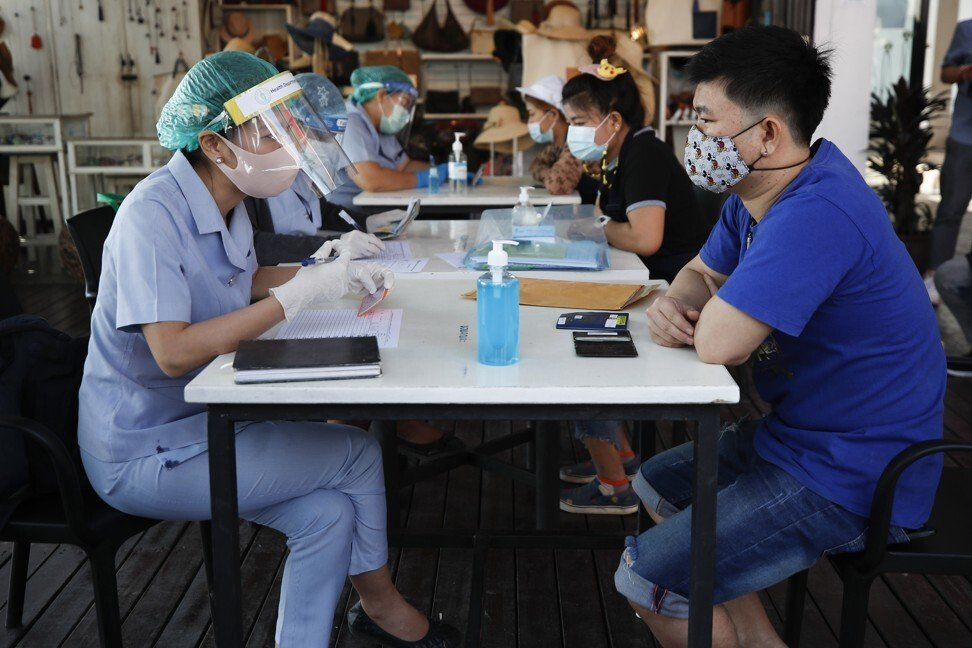 Migrant workers are screened by health workers at a food market in Bangkok on December 22, 2020. Photo: EPA-EFE