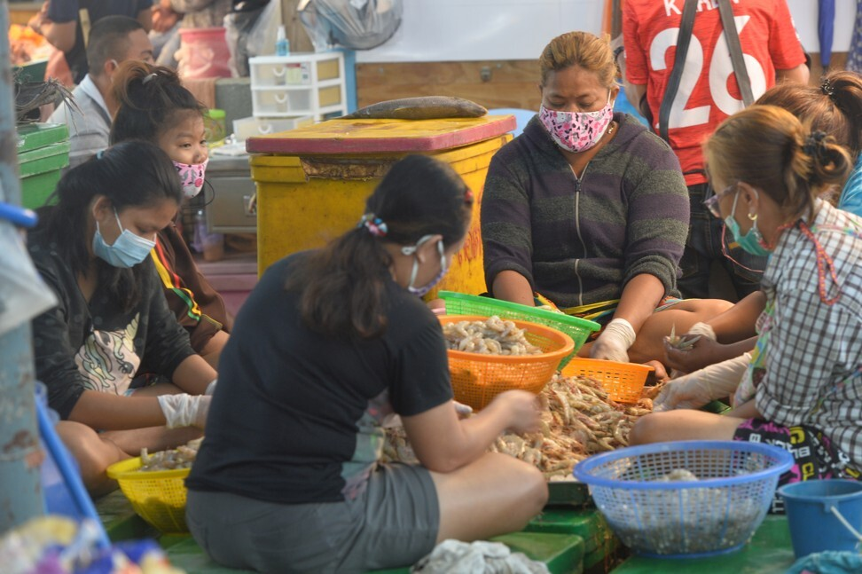 Workers clean shrimps in a market in Samut Sakhon province on December 21, 2020. Photo: Xinhua