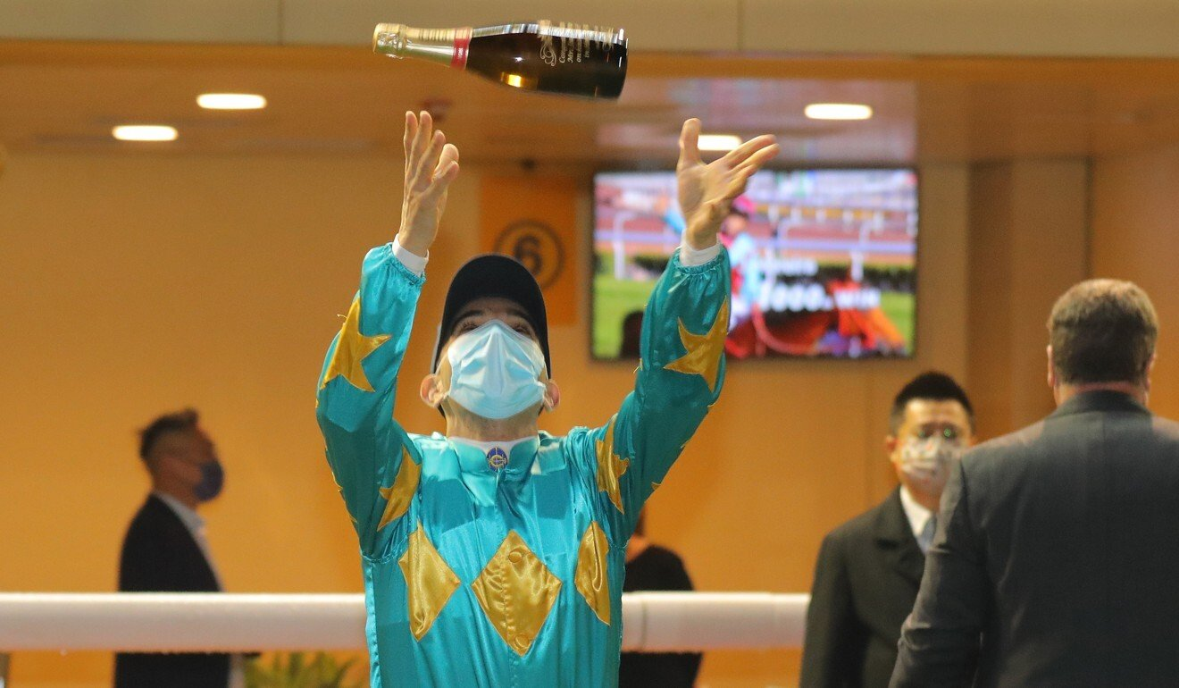 Joao Moreira throws a bottle of champagne up in the air to celebrate the milestone.