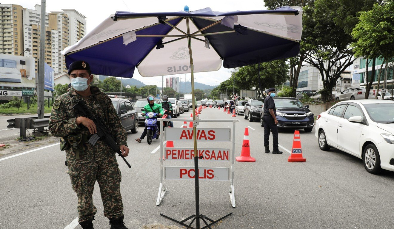 A soldier stands guard at a roadblock to enforce the lockdown in Kuala Lumpur. Photo: Reuters