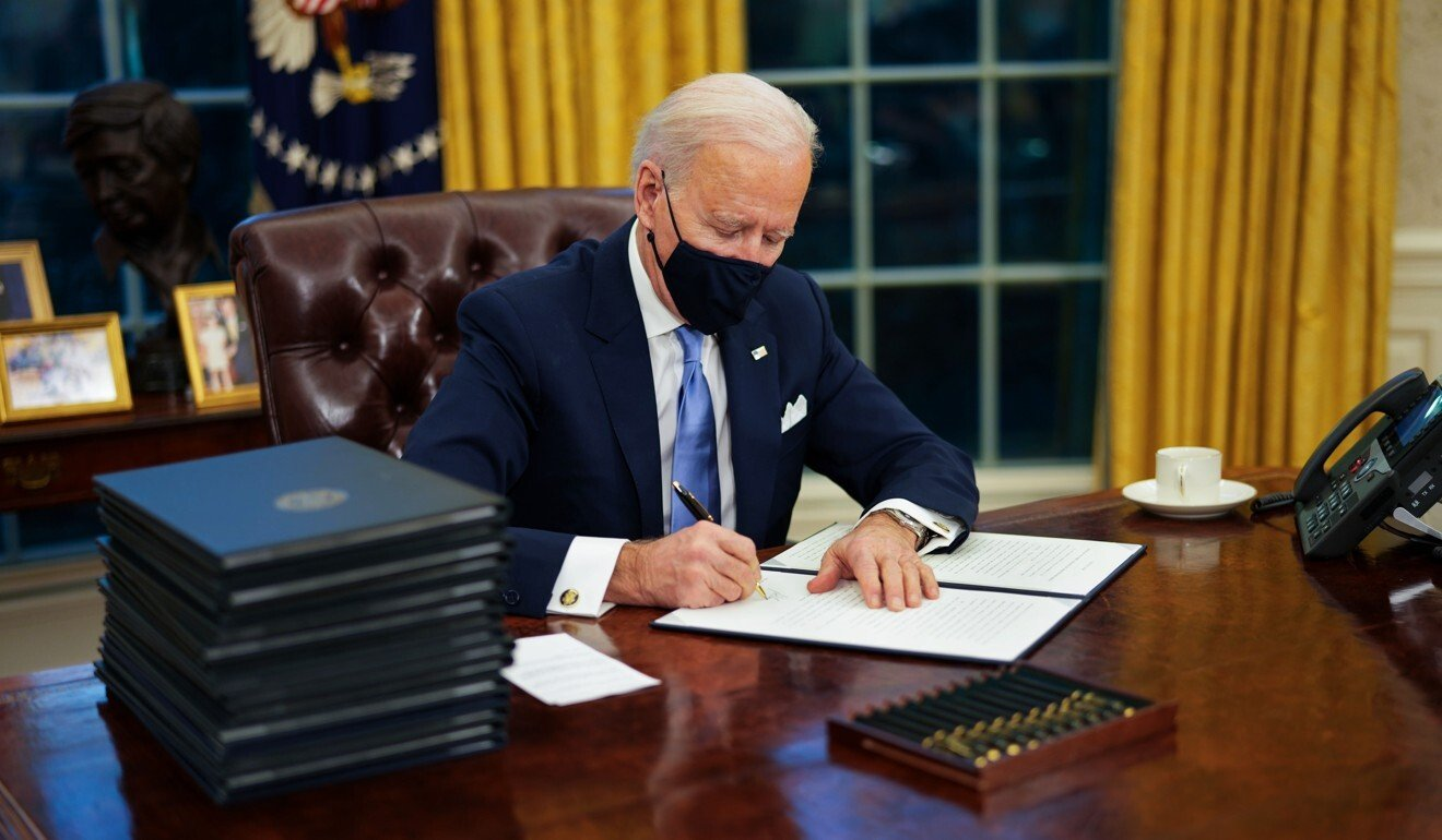 US President Joe Biden signs an executive order on Covid-19 during his first minutes in the White House's Oval Office on Wednesday. Photo: EPA-EFE