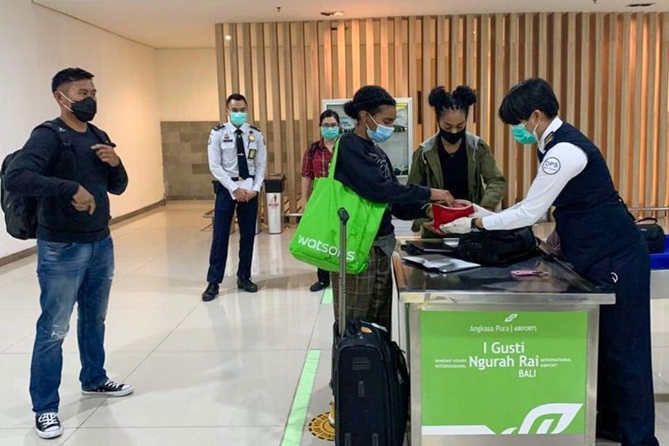 Kristen Grey, tengah, dan rekannya bersiap meninggalkan bandara Bali.  Foto: AFP