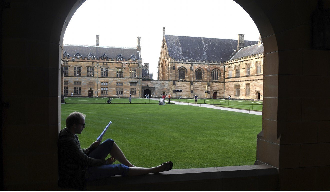 A student reads while sitting on a ledge at the Quadrangle of the University of Sydney, Australia. Photo: AP