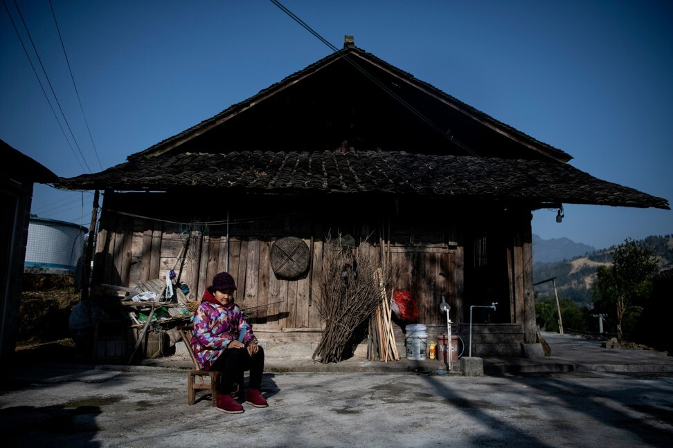 A woman sitting in front of her residence in Baojing county in central China's Hunan province on January 12, 2021. Photo: AFP