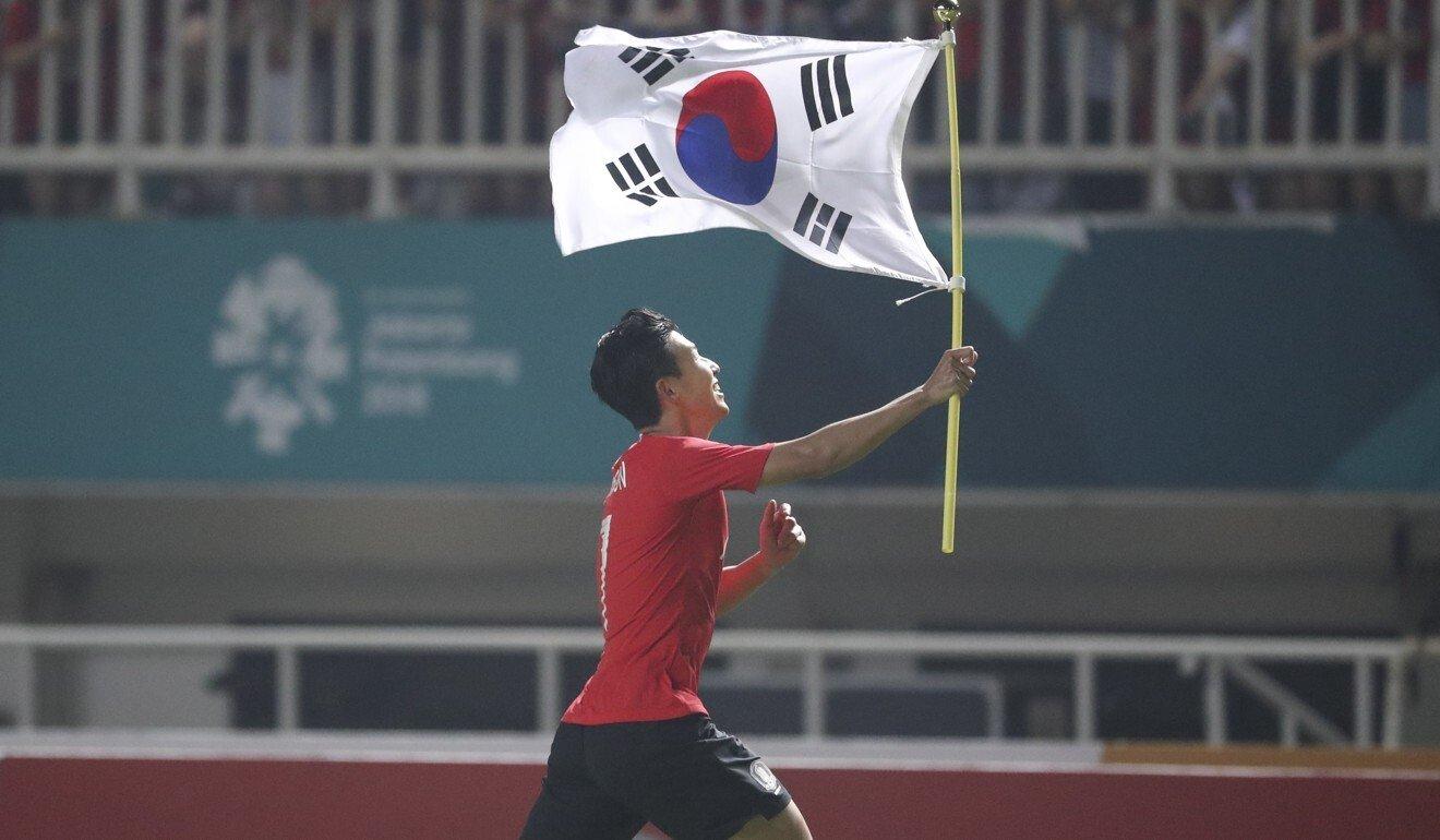 Son Heung Min của Hàn Quốc vẫy cờ tổ quốc sau khi giành huy chương vàng đồng đội tại Đại hội thể thao châu Á ở Indonesia năm 2018. Ảnh: EPA