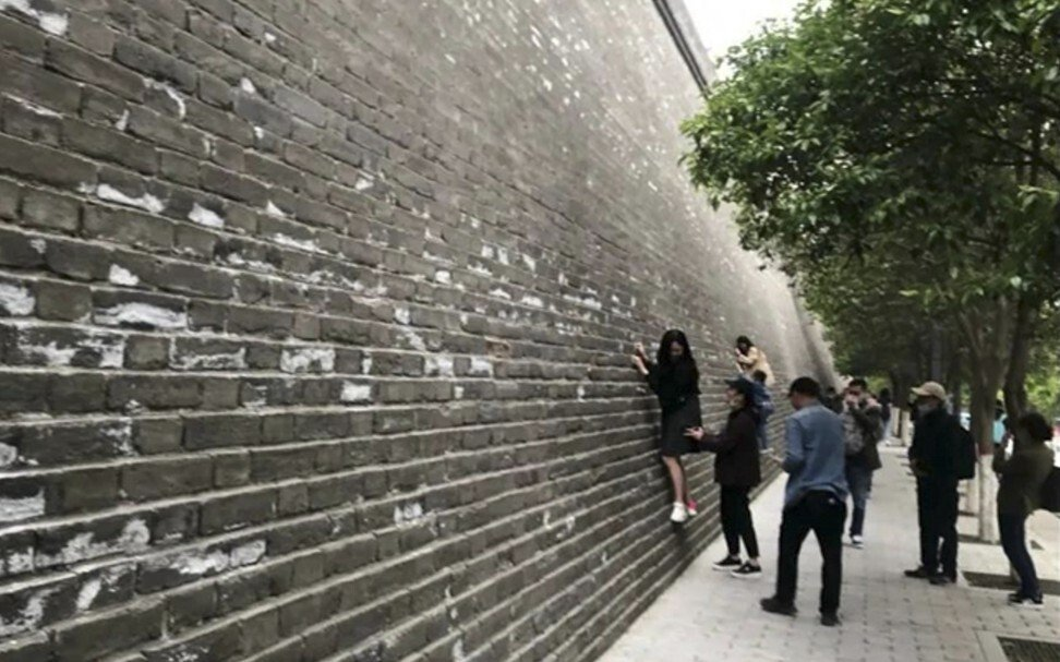 Tourists climbing and damaging the ancient city walls at Xian, centra China, despite requests they refrain from doing so. Photo: Handout