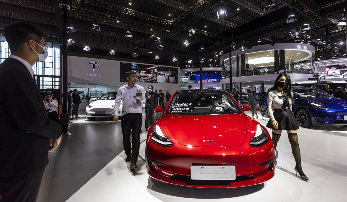 People walk by a Tesla Model 3 car during a media preview of the Shanghai Auto Show on April 19, 2021. Photo: EPA-EFE