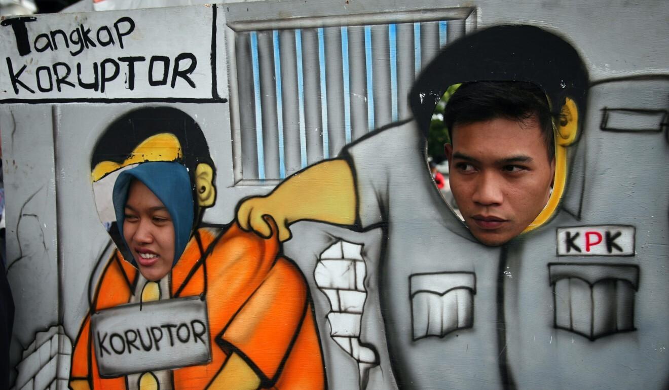 Sebuah papan kartun yang menggambarkan Komisi Pemberantasan Korupsi Indonesia menangkap pejabat korup di Malang, pulau Jawa timur  foto AFP