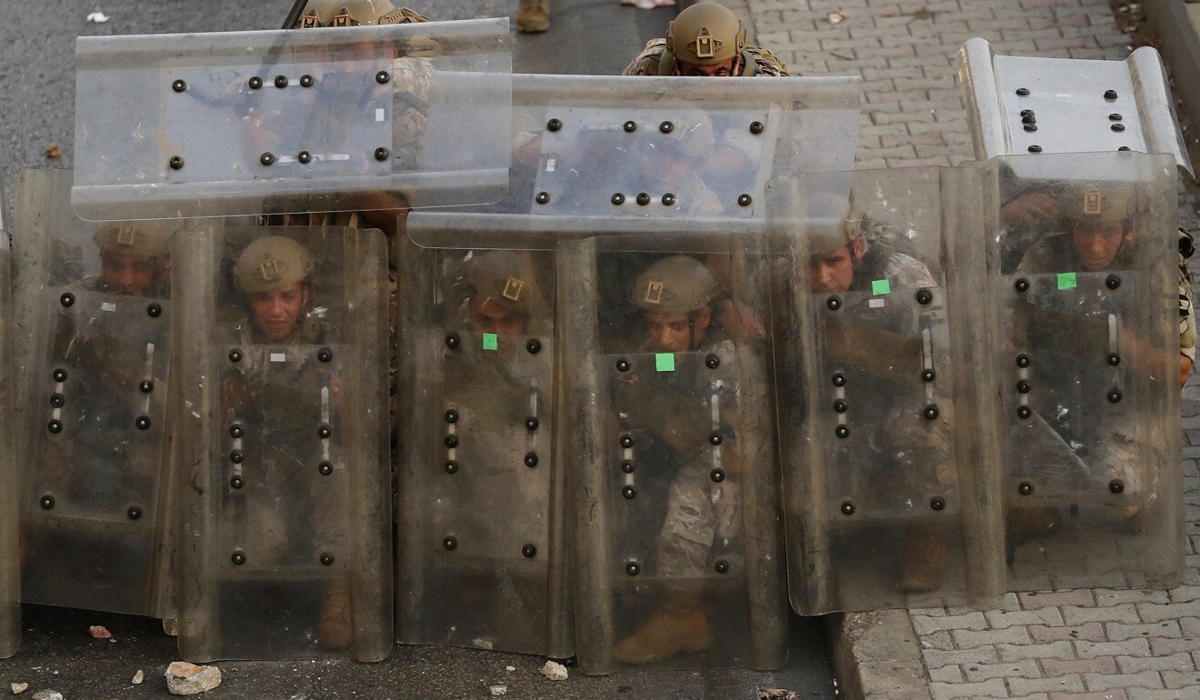 Lebanese soldiers in Beirut take cover from thrown projectiles. Photo: AP