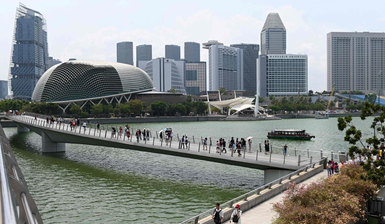 Visitors walk along the bridge leading to the Merlion park in Singapore. Photo: AFP