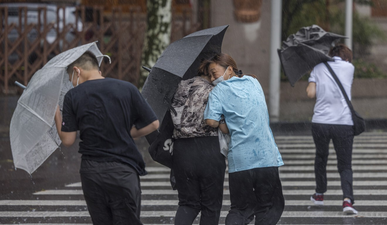 People in Shanghai use their umbrellas to brace against strong winds caused by Typhoon In-fa. Photo: EPA-EFE