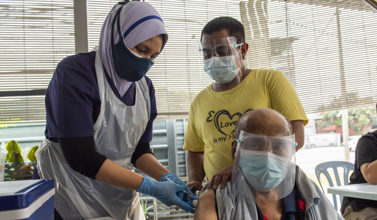 A Malaysian medical worker administers a Covid-19 vaccine to a senior citizen in Kuala Lumpur. Photo: Xinhua