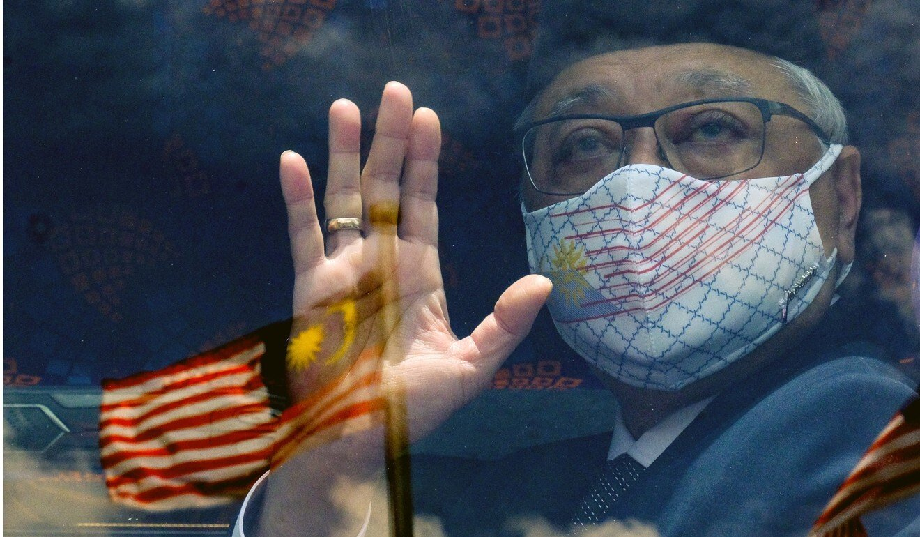 Ismail Sabri Yaakob waves from a bus with the Malaysian flag reflected in the window. Photo: Bloomberg