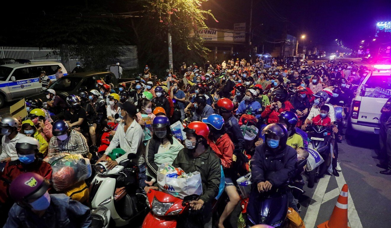 People, mostly migrant workers who are planning to return to their hometowns, wait at a checkpoint to leave Ho Chi Minh City. Photo: Reuters