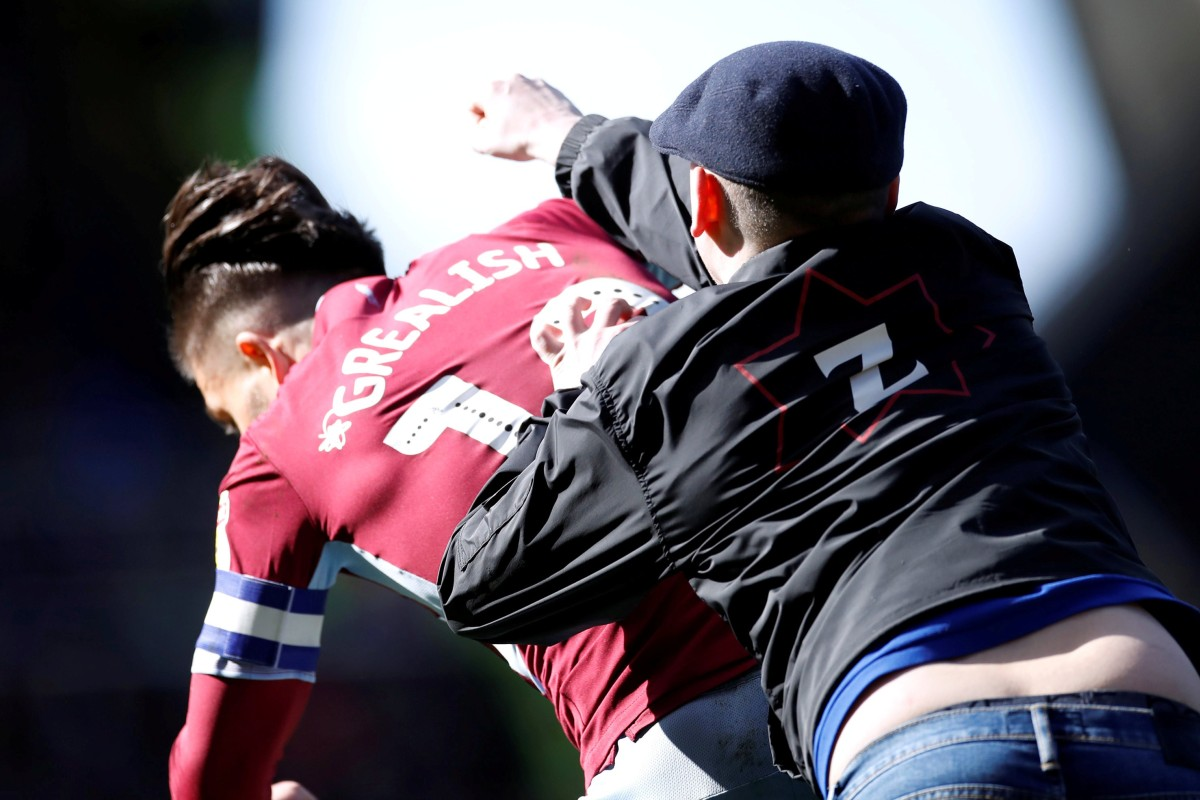 59d24686c A Birmingham City supporter invades the pitch and attacks Aston Villa s  Jack Grealish. Photo