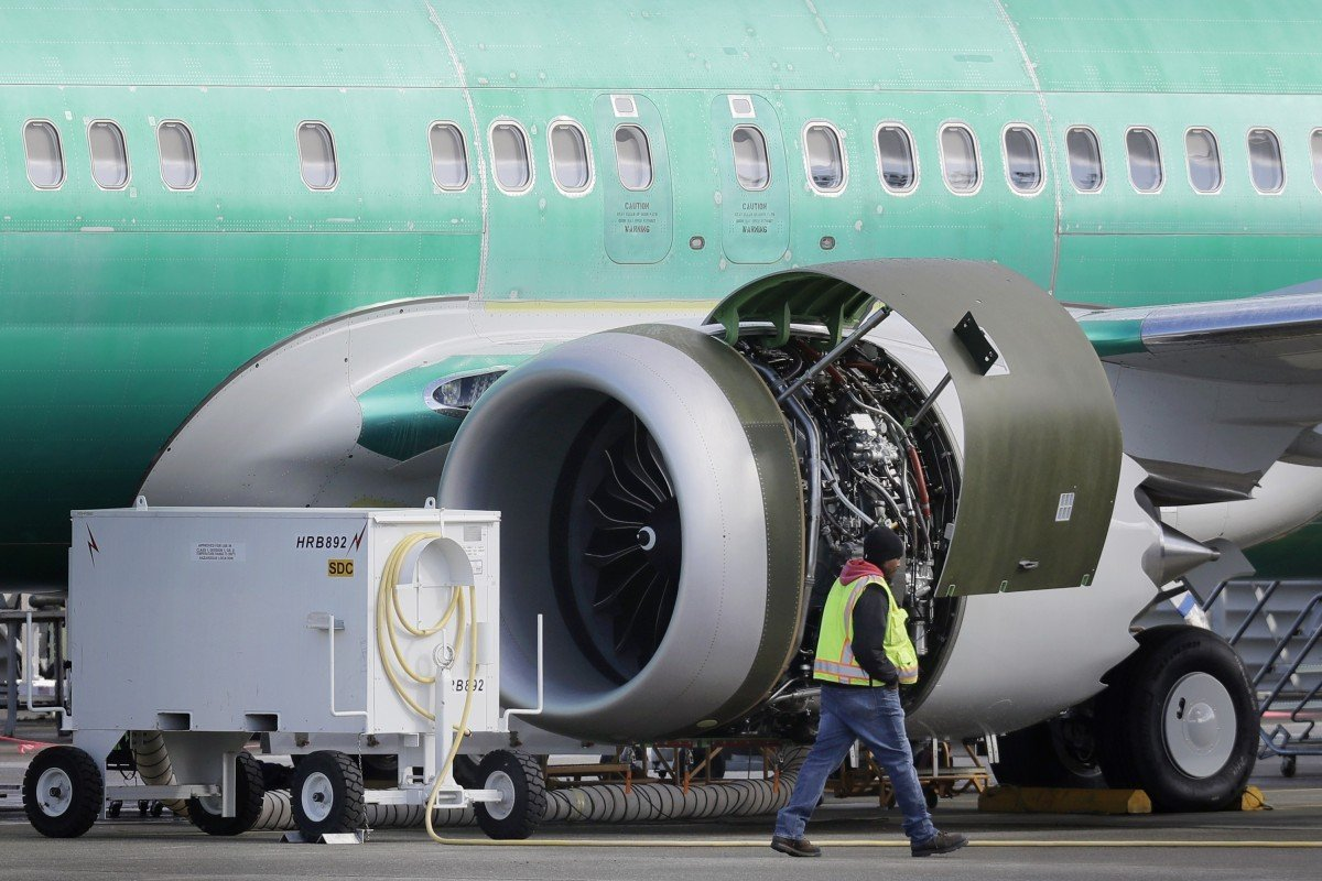 edafba38a A worker walks past an engine on a Boeing 737 MAX plane being built for  American