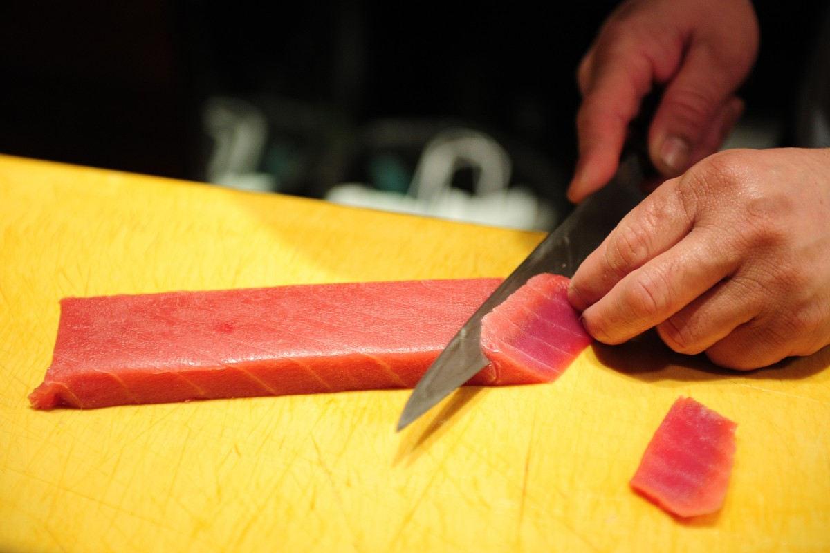 A sushi chef prepares tuna sashimi at an upscale Japanese restaurant in New York. Photo