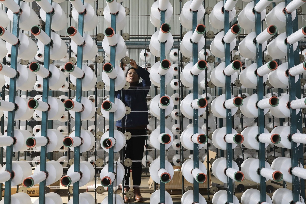 9f4151e6d6a A worker adjusts a cotton string roll at a textile factory in Hangzhou