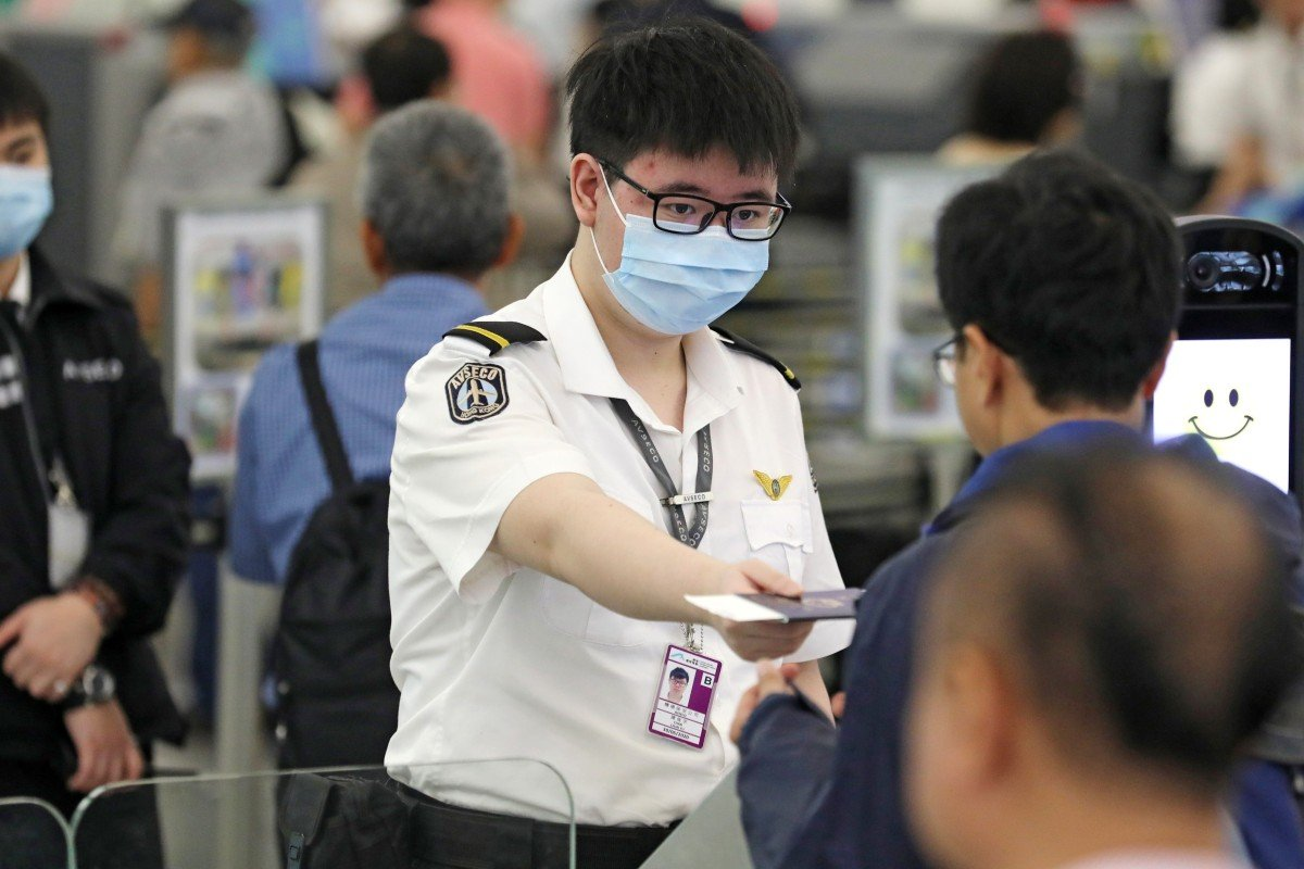 bf27107a0 Staff at Hong Kong International Airport in Chek Lap Kok wearing surgical  masks amid the outbreak