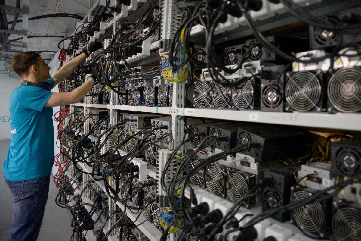 An employee inspects machines for the production of bitcoin and lightcoins. Photo: AFP