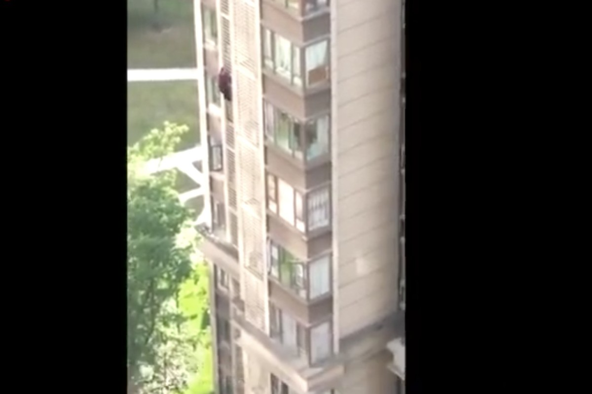 The elderly woman with Alzheimer's climbs down the outside of her residential building in Chengdu, Sichuan province, on Thursday. Photo: Weibo