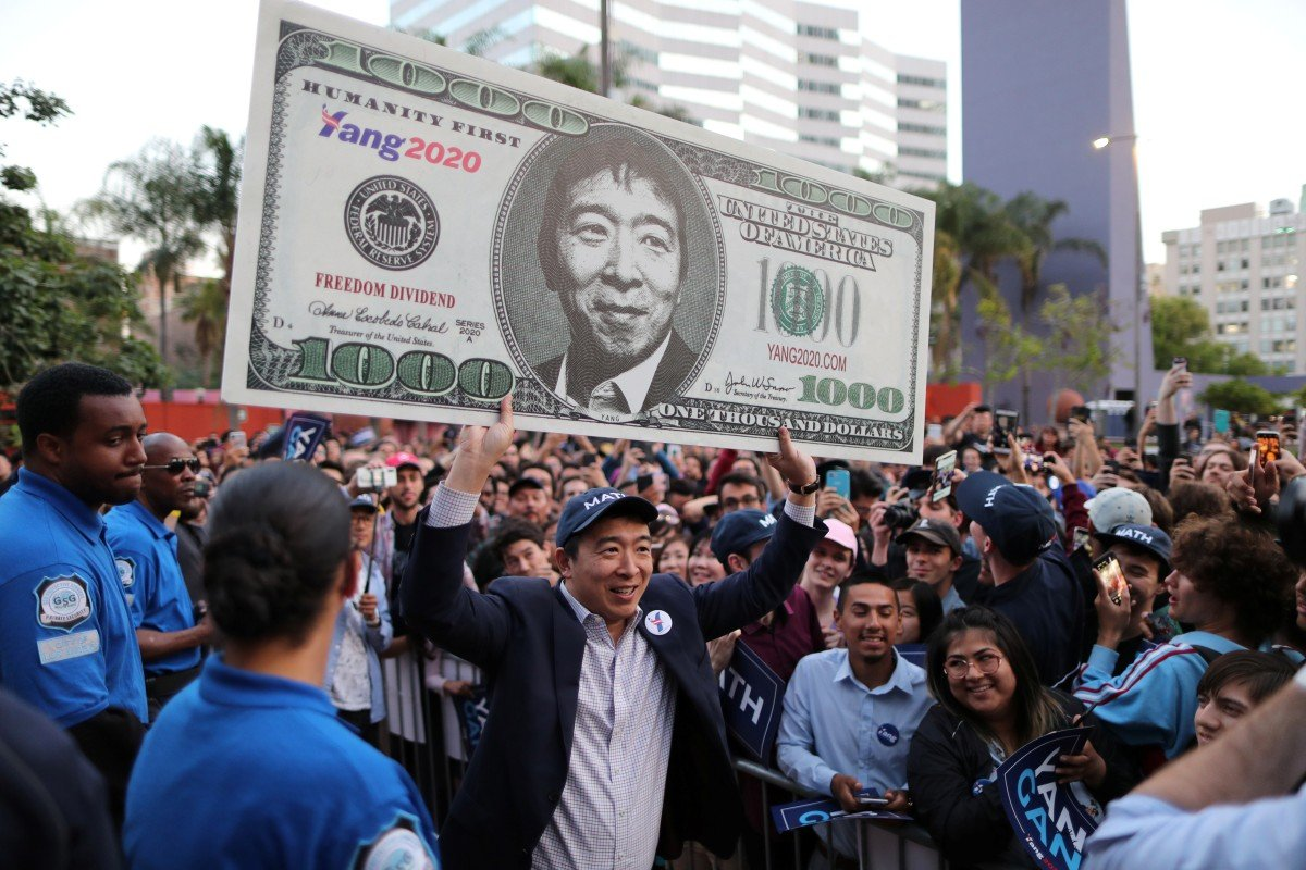Us democratic presidential candidate andrew yang hoists a supporters sign after speaking at a rally in