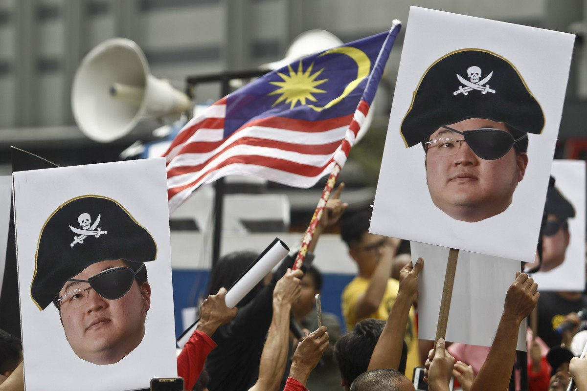 Protesters hold portraits of Jho Low illustrated as a pirate during a protest in Kuala Lumpur, Malaysia. The new police chief has called the fugitive back to face charges in the 1MDB case. Photo: AP