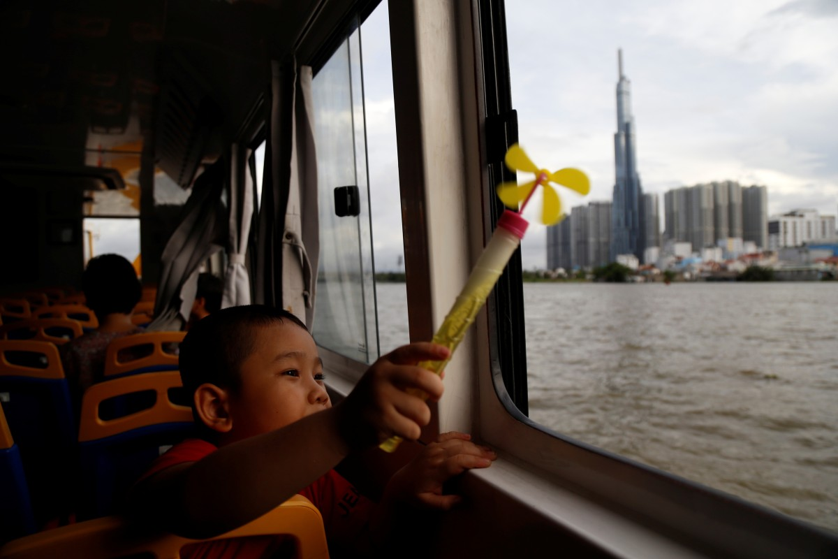 A a child on a Saigon waterbus brandishes a pinwheel as he passes Landmark 81, Vietnam's tallest building, in Ho Chi Minh City on June 6. While Vietnam has enormous potential for wind and solar power generation, funding for coal-power electricity plants under China's Belt and Road Initiative could derail its renewable energy push. Photo: Reuters