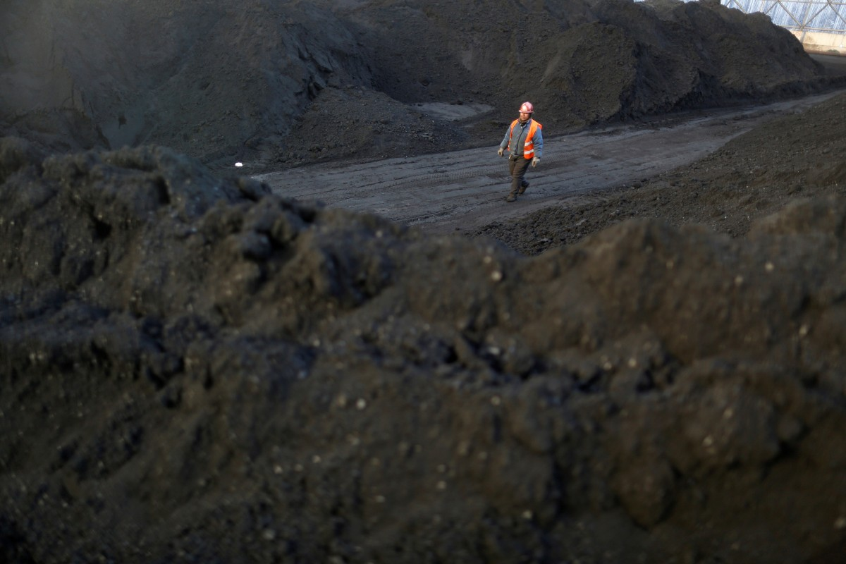 A worker walks past coal piles at a coal coking plant in Yuncheng, Shanxi province, one of China's heavily industrial regions in the North. Photo: Reuters
