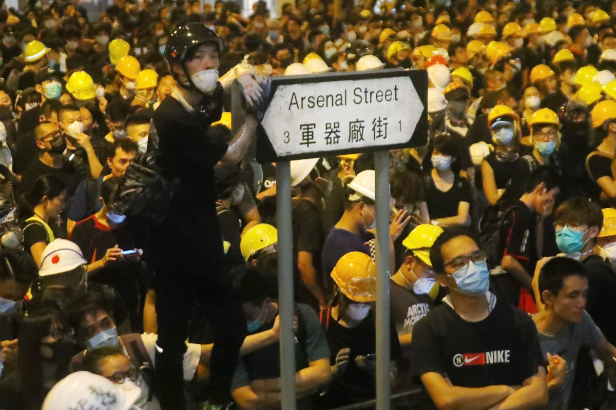 Protesters wear their trademark yellow helmets as they gather outside police headquarters in Wan Chai on June 22. Photo: Edmond So