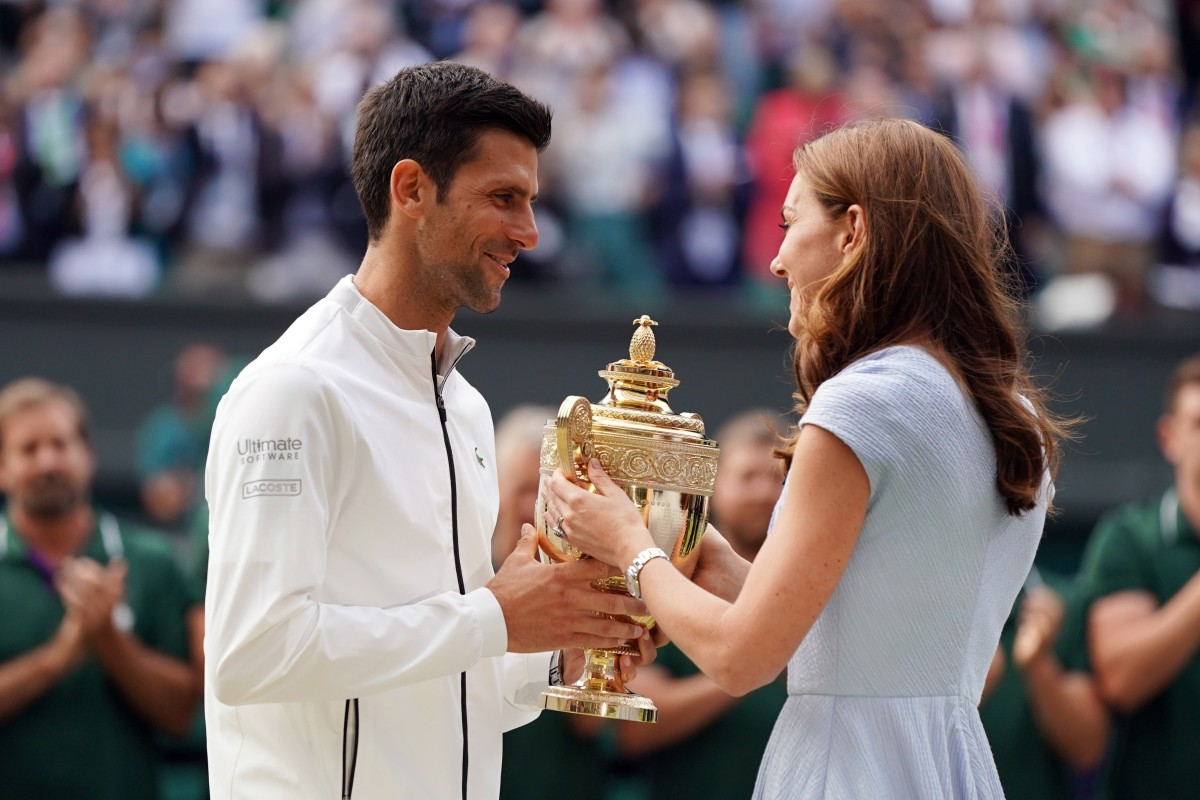 Novak Djokovic receives the trophy from Catherine the Duchess of Cambridge after beating Roger Federer on Sunday. Photo: EPA