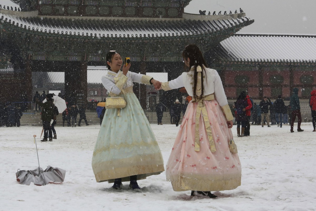 A woman takes a picture in the snow in Seoul, South Korea. Photo: AP