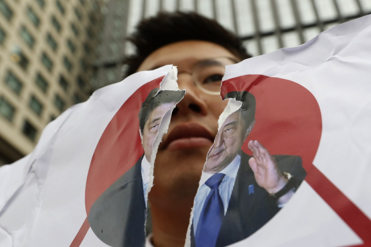 A protester in Seoul holds a defaced image of Japanese Prime Minister Shinzo Abe during a rally denouncing the Japanese government on July 17. Photo: AP