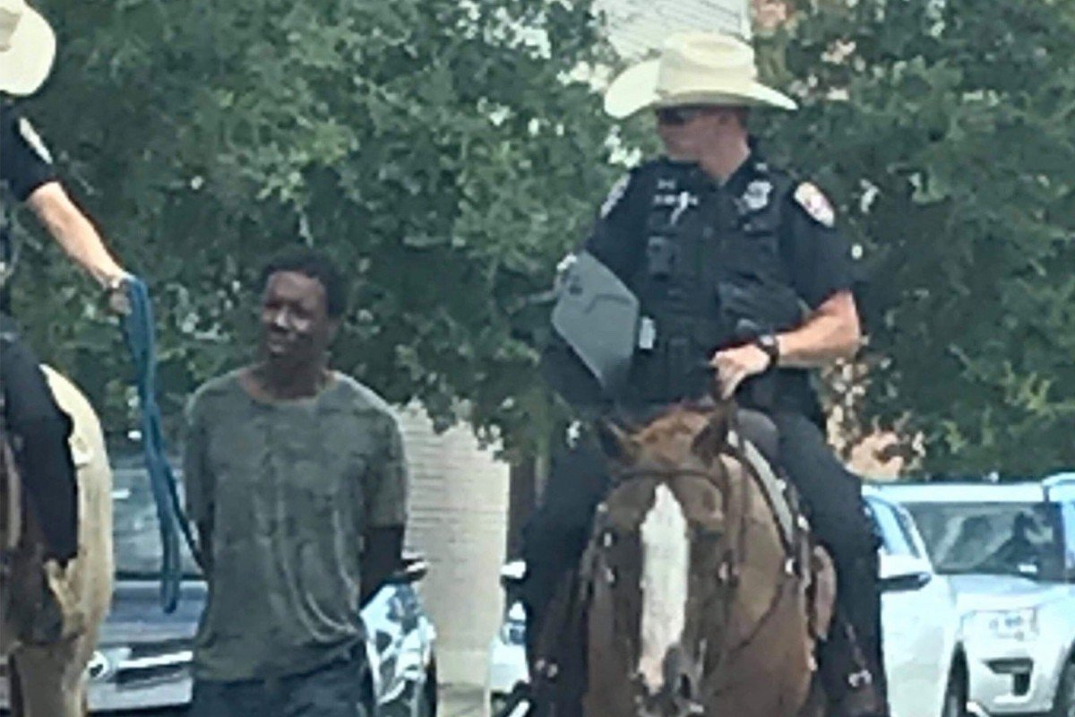 Photo of two white Texas police on horseback leading black man